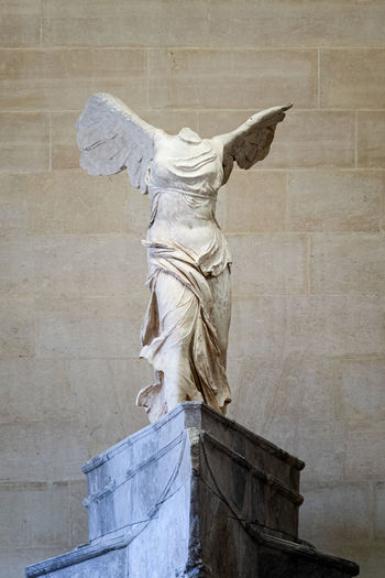 Low angle view of angel statue against wall