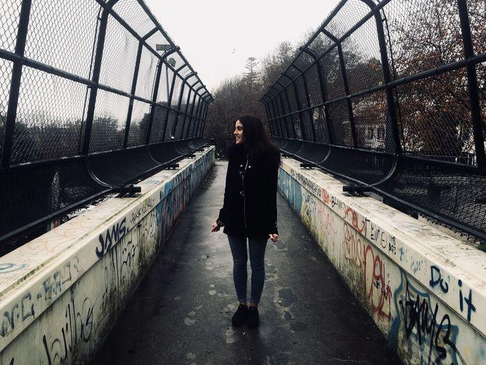 Full length of woman standing on footbridge