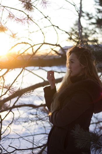 Side View Of Young Woman In Warm Clothing Standing By Trees During Sunset