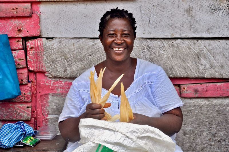 Portrait of smiling vendor selling corns against wall