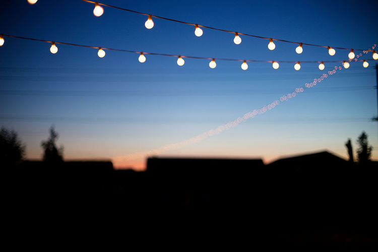 Silhouette illuminated lights against clear sky at night