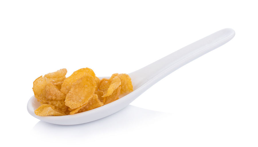 Corn flakes in spoon on white background Bowl Close-up Copy Space Crockery Cut Out Eating Utensil Food Food And Drink Freshness Fried Indoors  Kitchen Utensil No People Ready-to-eat Serving Size Snack Spoon Still Life Studio Shot Unhealthy Eating White Background