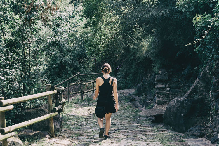 Girl walking along a small path in the mountain of sadernes, spain. on a sunny summer day