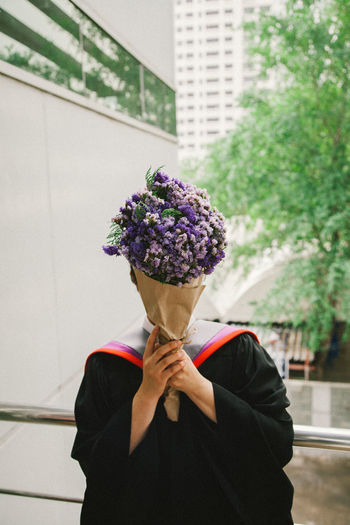 Person covering face with bouquet while wearing graduation gown against buildings in city