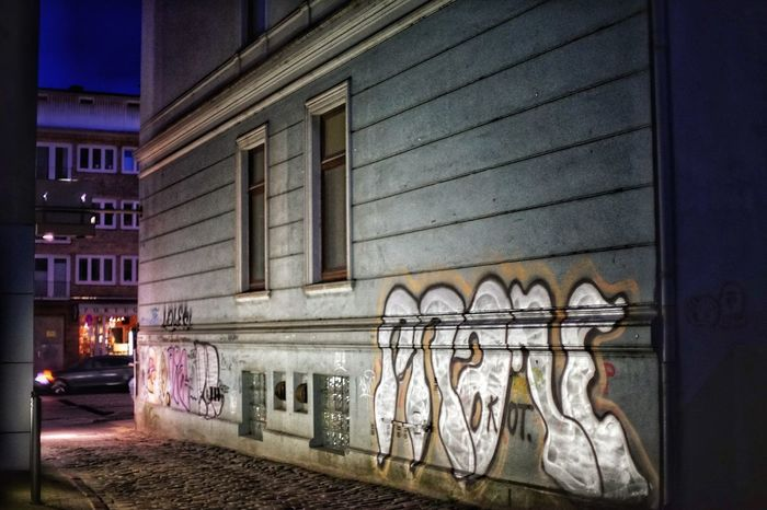 Graffiti in the Backyard Hidden Place  Backyard Architecture Building Exterior Built Structure No People Illuminated Building Night City Window Reflection Wall - Building Feature Dusk Glass - Material Graffiti Residential District Mode Of Transportation Side By Side Street Outdoors