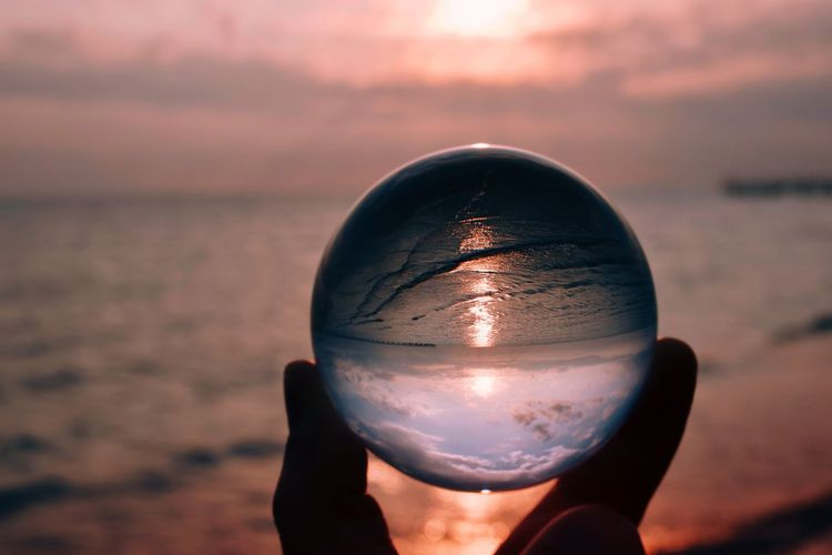 Close-up of hand holding crystal ball against sea during sunset