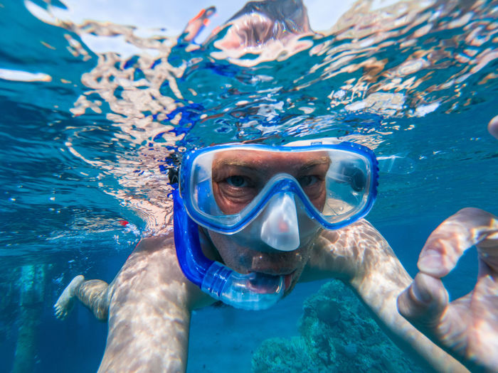 Snorkeling guy underwater doing scuba ok sign in the Red sea Egypt Exploring Snorkeling Aquatic Sport Coral Reef Eyewear Holiday Leisure Activity Lifestyles One Person Outdoors Portrait Red Sea Sea Shirtless Snorkel Snorkeling Sport Swimming Swimming Goggles UnderSea Underwater underwater photography Vacations Water