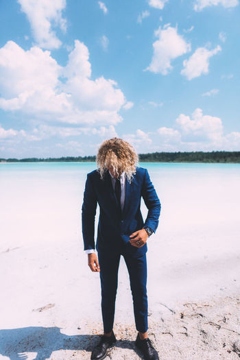 Blond curly man dressed in business suit is posing on the crystal clear lake. Trendy hairstyle, awesome shoot. Summer time. Beach Beauty In Nature Cloud - Sky Day Full Length Hair Hairstyle Land Leisure Activity Lifestyles Nature One Person Outdoors Real People Rear View Scenics - Nature Sea Sky Standing Water Women