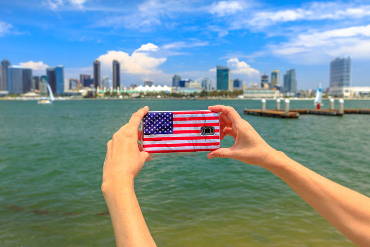 Closeup of tourist takes photo of San Diego By skyline by mobile phone with American flag cover. Blonde woman takes pictures in California summer holidays with her smartphone from Coronado Island, USA San Diego San Diego, California United States America American American Flag Women Mobile Phone Picture Woman Girl Tourist Skyline Beach Cityscape Seascape Built Structure Architecture One Person Real People Building Exterior Leisure Activity Nature Lifestyles Holding City Sky Outdoors Skyscraper Office Building Exterior Human Hand Water Hand Human Body Part Focus On Foreground Flag