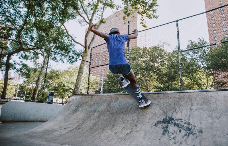 Full length of man jumping against trees