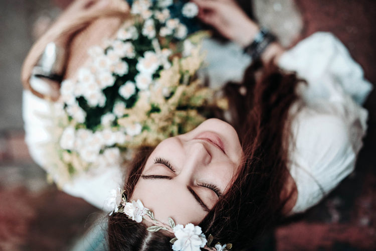 Young hippie woman with flowers on her head and closed eyes. summer concept of youth and freedom