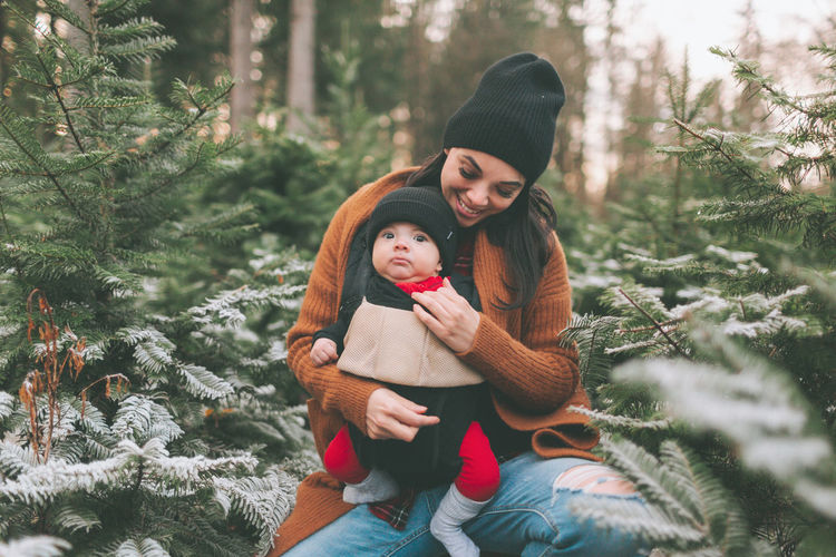 A mother wearing her baby at a Christmas tree farm in winter. Togetherness Bonding Family Child Warm Clothing Love Baby Mother Carrier Tree Farm Christmas Tree Farm Winter Cold