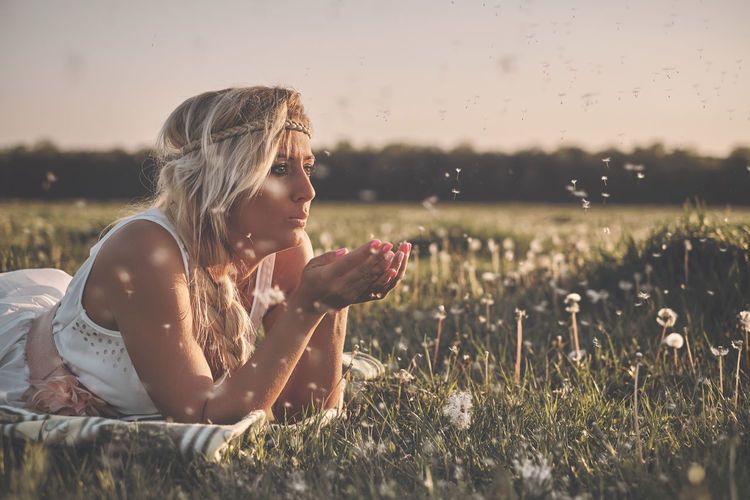 Casual Clothing Contemplation Dandelion Field Girls Grass Hairstyle Land Leisure Activity Lifestyles Nature One Person Outdoors Plant Real People Selective Focus Sitting Sky Sunlight Teenager Women Young Adult Young Women