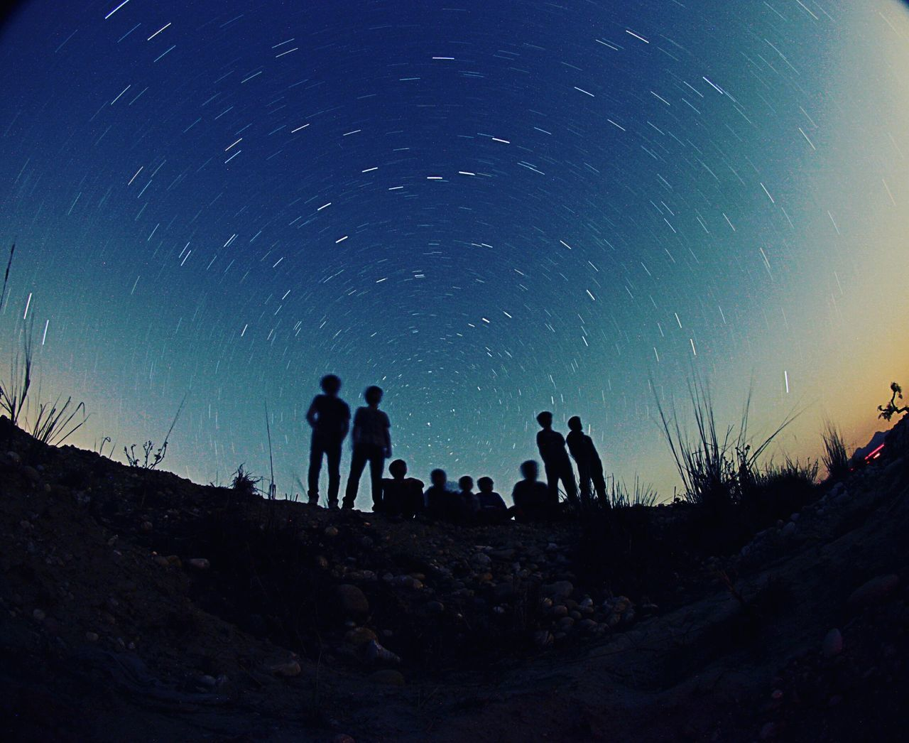 Fish-Eye View Of Silhouette People On Field Against Star Trails