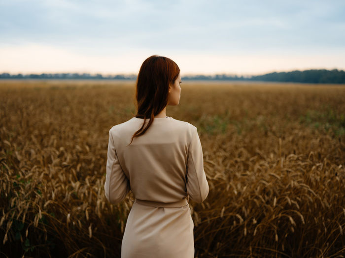 Rear view of woman standing in field