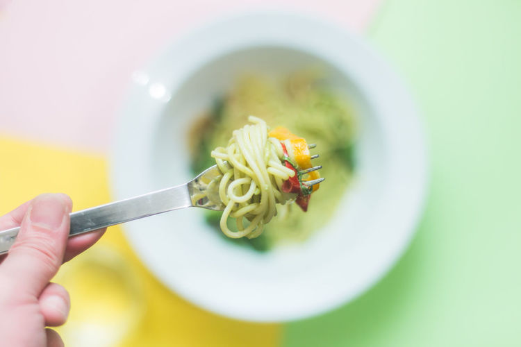 Cropped Image Of Hand Holding Noodles In Fork