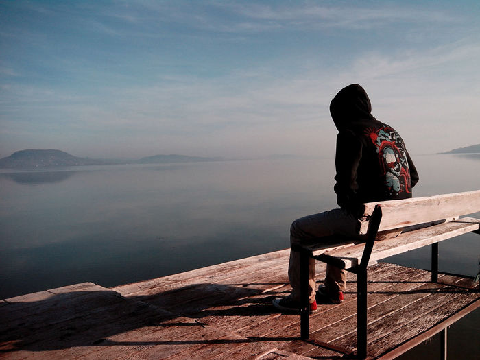 Man sitting on bench against sea