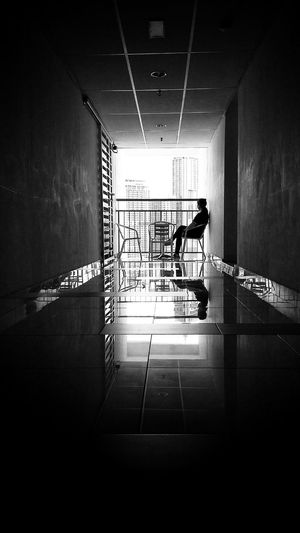 A shot in black and white of a lady sitting on a chair at a balcony of an apartment facing skyscrapers Balcony Rear View Back Shot  Alone Woman Lonely Woman Silhouette Blackandwhite Woman Hallway Woman Sitting Black And White Photography Chairs And Table Skyscrapers Alone