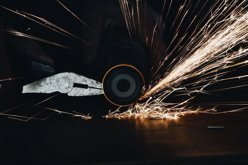 Man using rotary grinder and sparks flying Long Exposure Sparks Motion No People Night Wire Wool Indoors  Metal Industry Circular Saw Rotary Grinder Sparks Flying Sparks On Black Background Industrial Industry Working Hands Industrial Photography Industrial Equipment Capture Tomorrow Humanity Meets Technology