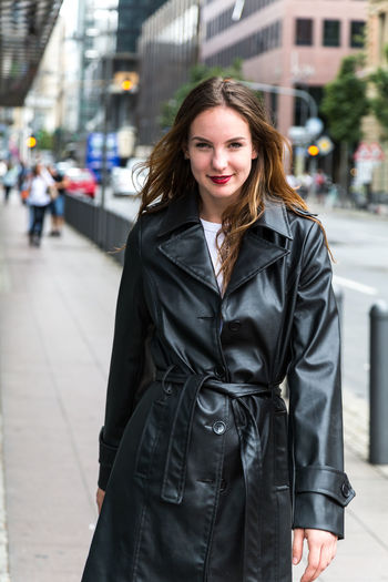 Portrait of young woman wearing a trench coat in city One Person Looking At Camera Beautiful Woman Trench Coat Fashion Beauty Lipstick Attractive Woman Urban Caucasian Young Adult Outdoors Day Autumn Brunette Brown Hair Three Quarter Length Front View City Smile