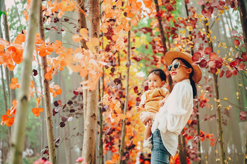 Smiling mother with son standing against autumn tree in forest