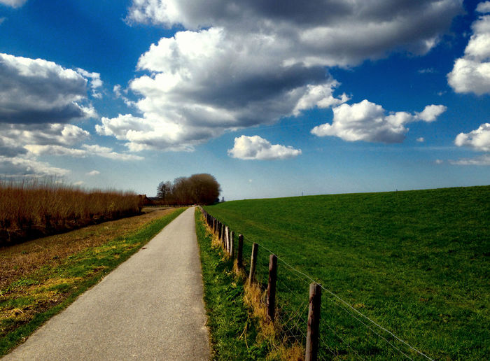 Road leading towards field against cloudy sky