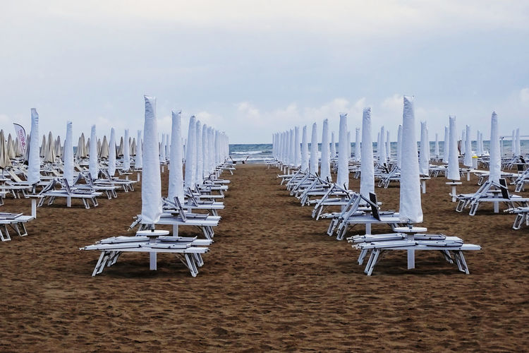 Empty chairs and beach umbrellas against sky