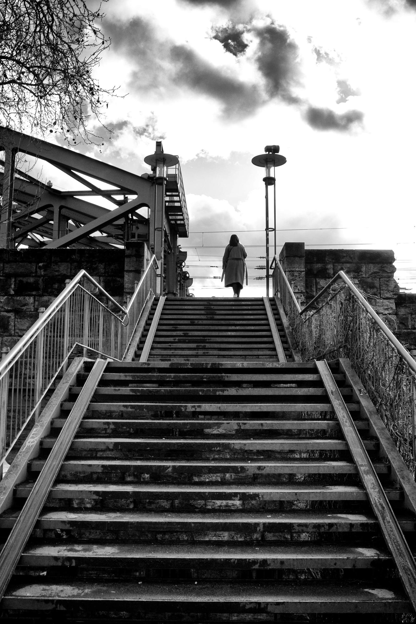 staircase, steps and staircases, architecture, railing, sky, stairs, built structure, black and white, one person, cloud, the way forward, monochrome, monochrome photography, full length, nature, men, low angle view, lifestyles, adult, black, day, walking, outdoors, rear view, women, leisure activity, building exterior, standing, transportation