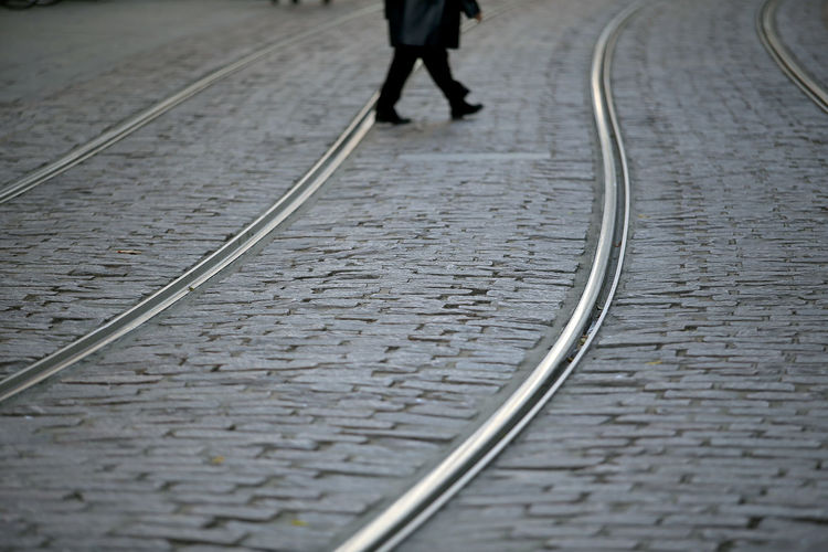 Low section of person walking on railroad track