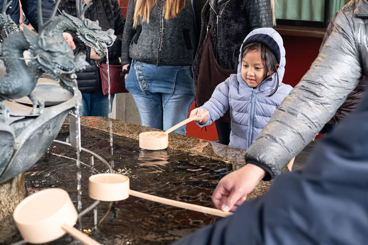 People with ladle by fountain at shrine