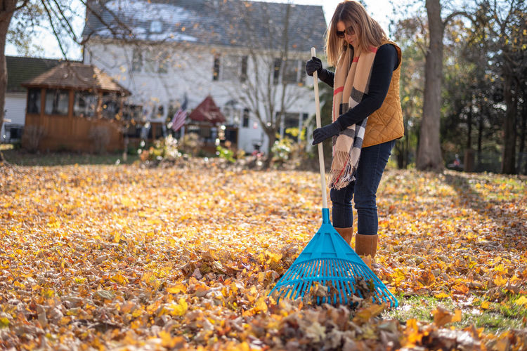 Full length of woman cleaning autumn leaves on land