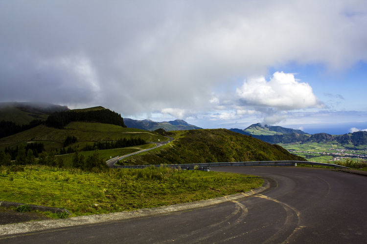 Rural road leading through green hills Asphalt Azores Country Field Grass Green Color Rolling Landscape Rural Scenic Travel Cloud - Sky Direction Environment Green Island Hill Landscape Mountain Nature No People Non-urban Scene Outdoors Remote Road Road Trip Scenics - Nature