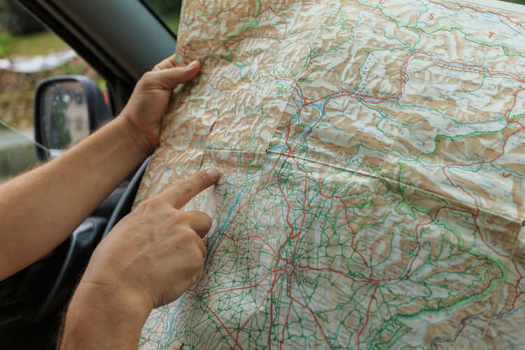 Cropped image of hand pointing at map while sitting in car