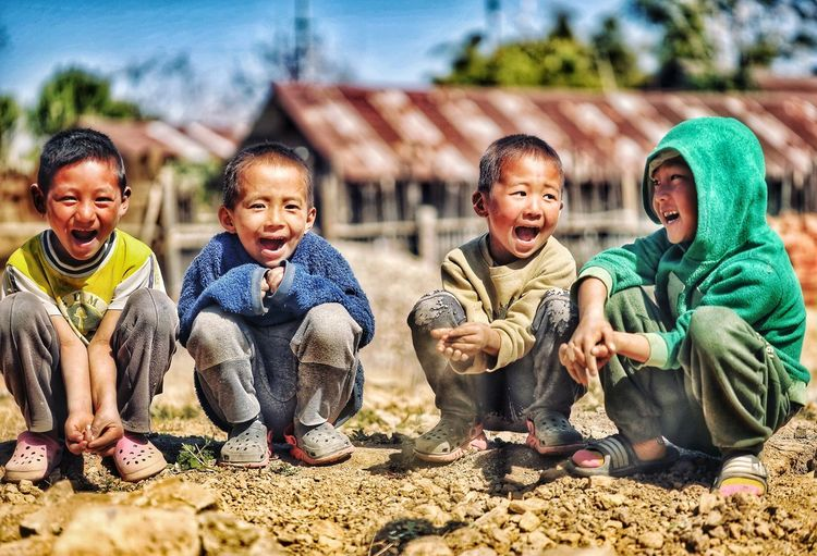 Group of children sitting outdoors and laughing