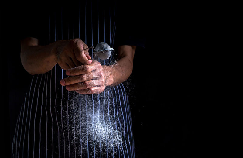 Chef sprinkle icing sugar on the donut. male baker sprinkles icing sugar on black background.