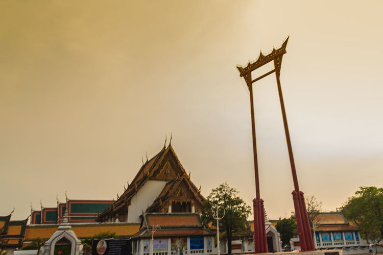 Vintage view of the Giant Swing, a religious structure which located in front of Wat Suthat temple. It was used in the Brahmin ceremony and is one of Bangkok famous tourist attraction. Crowd Of Pigeon Giant Swing Giant Swing Bangkok Red Giant Swing Sao Ching Cha Tourist Attraction  Wat Suthat Wat Suthat Thepwararam Architecture Belief Building Building Exterior Built Structure City Clear Sky Dusk House Low Angle View Nature No People Outdoors Place Of Worship Religion Residential District Sky Spirituality Sunset Tourist Attraction In Thailand Tourist Attractions Tourist Attractions, Tourist Destinations, City Life, Leisure Activities,