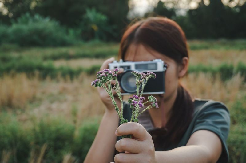 Woman Photographing Purple Flowers On Field