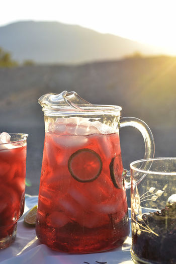 Pitcher and drink glasses of hibiscus flower iced tea in mojave desert setting