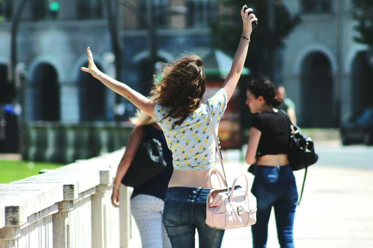 Rear view of excited woman with arms raised walking on footpath