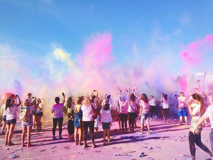 People Celebrating Holi Festival Outdoors Against Sky