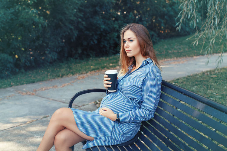 Pregnant young woman sitting on bench in park
