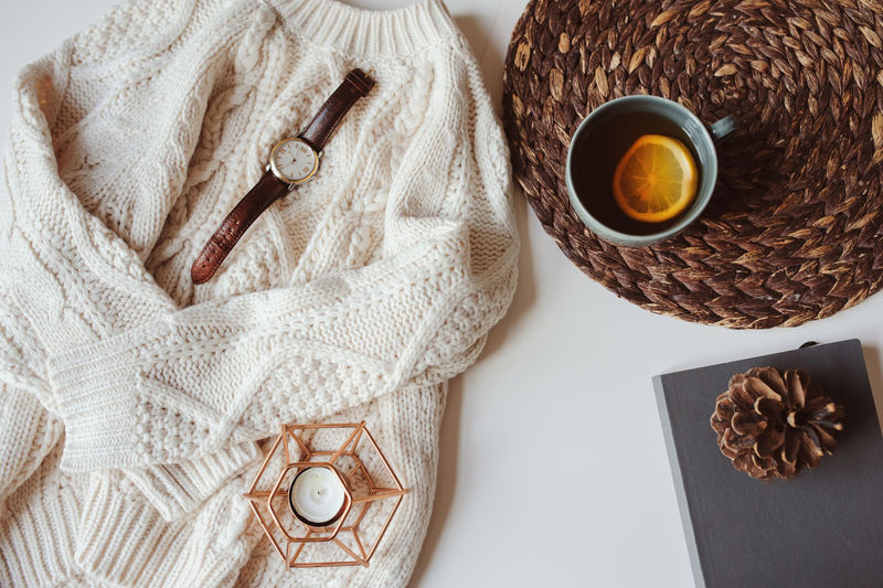 fall or winter cozy still life set. Warm knitted sweater, cup of tea with lemon, and book with pine cone on white background. Hygge concept. Candle Relaxing Weekend Winter Casual Clothing Close-up Cozy Cup Directly Above Drink Flat Lay High Angle View Hygge Indoors  Knitted  Mug No People Outfit Still Life Sweater Table Textile