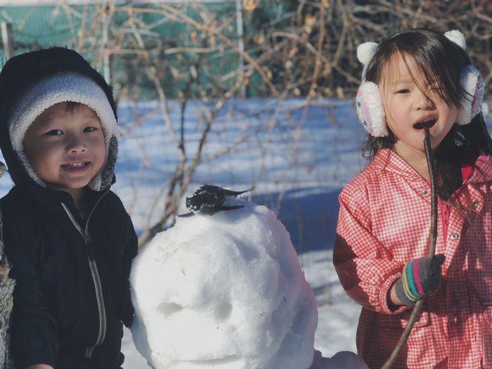 Portrait of cute siblings standing by snow on field