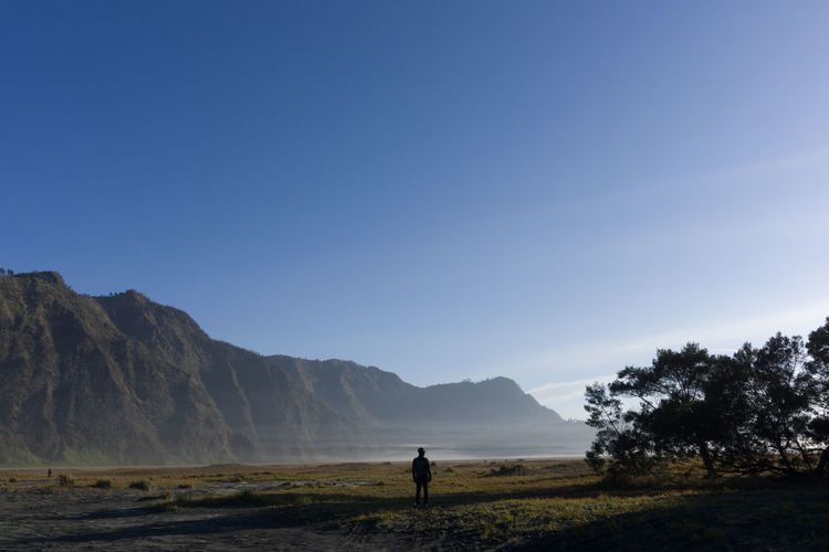Man standing on mountain against clear sky mount bromo