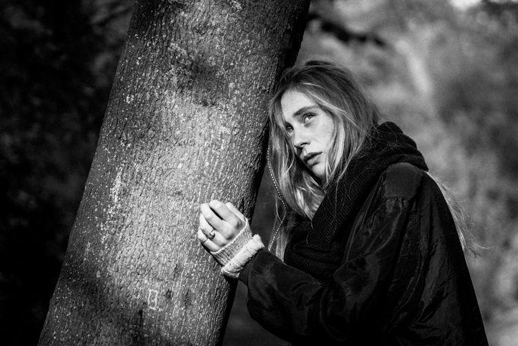 Portrait of woman against tree trunk