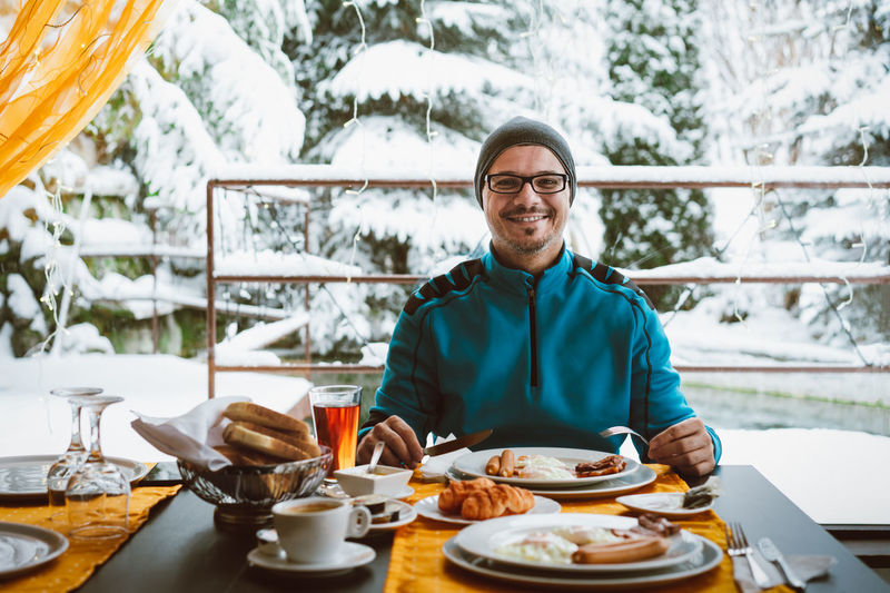 Breakfast in paradise. Winter Snow Snow Covered Trees Window Window Frame Window View Breakfast Table Portrait Men Smiling Happiness Sitting Prepared Food Served Serving Size Dish Pastry Plate Ready-to-eat