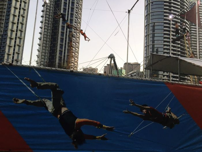 A trapeze instructor reaches to a student during a training session at the Flying Trapeze Philippines in Bonifacio Global City, in Taguig, Metro Manila. Building Exterior Low Angle View Built Structure Architecture City Real People Day Skyscraper Outdoors Sky Trapeze Flyingtrapeze Aerobatics Flying High The City Light Philippines Manila Flying Trapeze