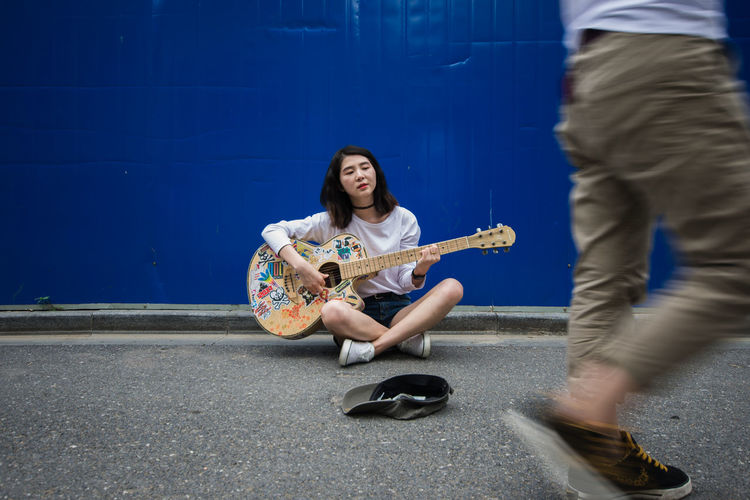 Woman Playing Guitar Against Blue Wall