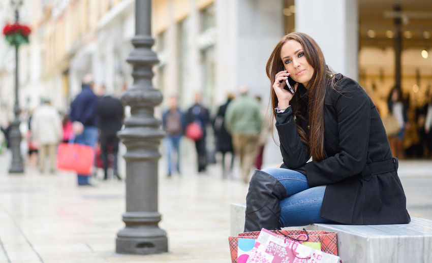 Thoughtful young woman talking on phone while sitting on seat in city