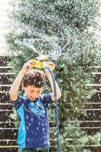 Cooling off. Boys Cheerful Child Childhood Children Only Day Drop Fun Happiness Males  Motion Nature One Boy Only One Person Outdoors People Playing Refreshment Splashing Spraying Sprinkler Water Wet